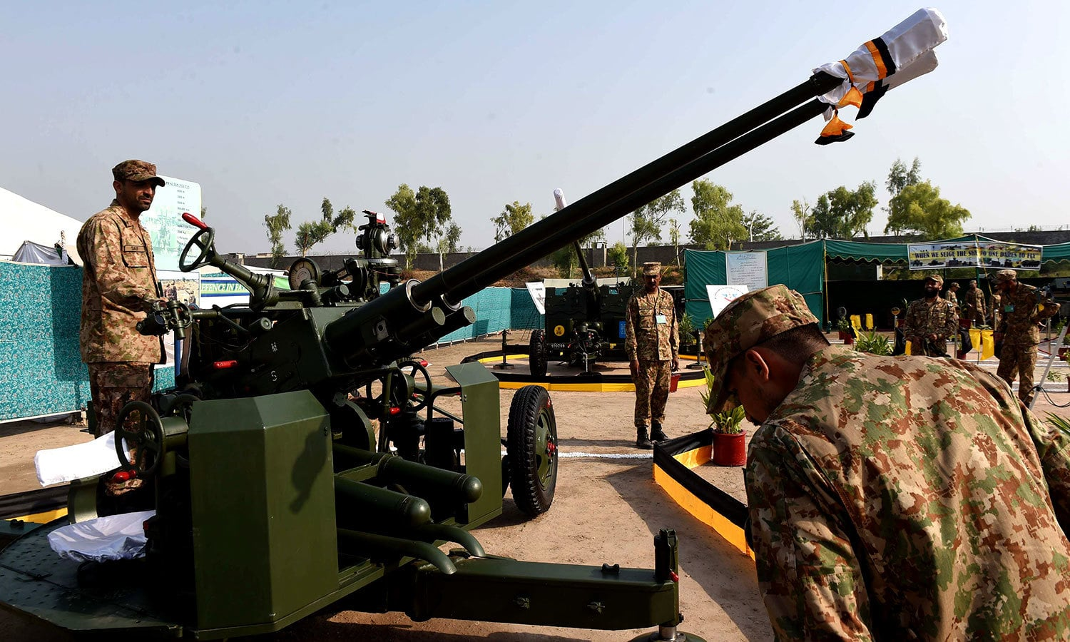 Soldiers stand along an anti-aircraft gun. — AFP