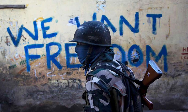 "An Indian paramilitary soldier walks past graffiti — demanding freedom ""Azadi"" — on a wall in Srinagar. ─ AP"