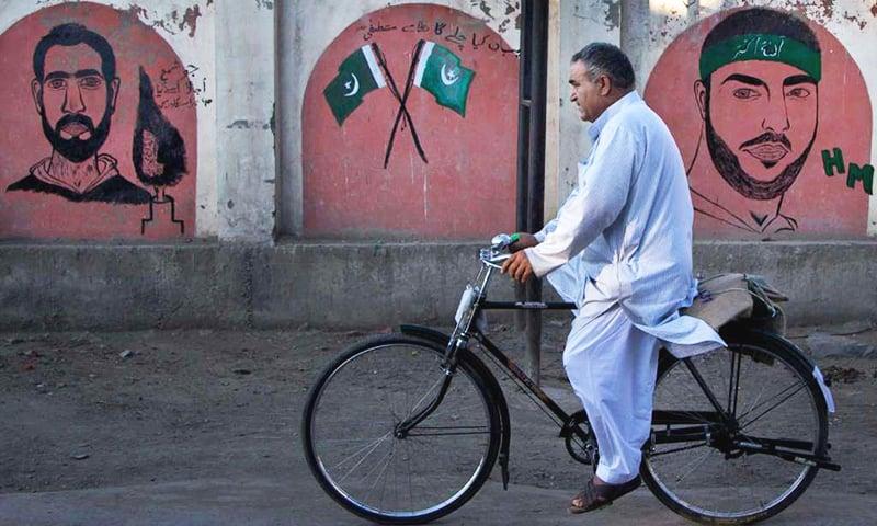 A Kashmiri man cycles past graffiti images of Burhan Wani.— AP