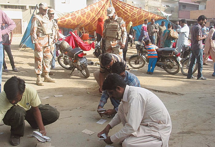 Workers of the Muttahida Qaumi Movement collect their poll-related matarial after a clash with activists of the Mohajir Qaumi Movement (Haqiqi) outside a polling station on Thursday.—PPI