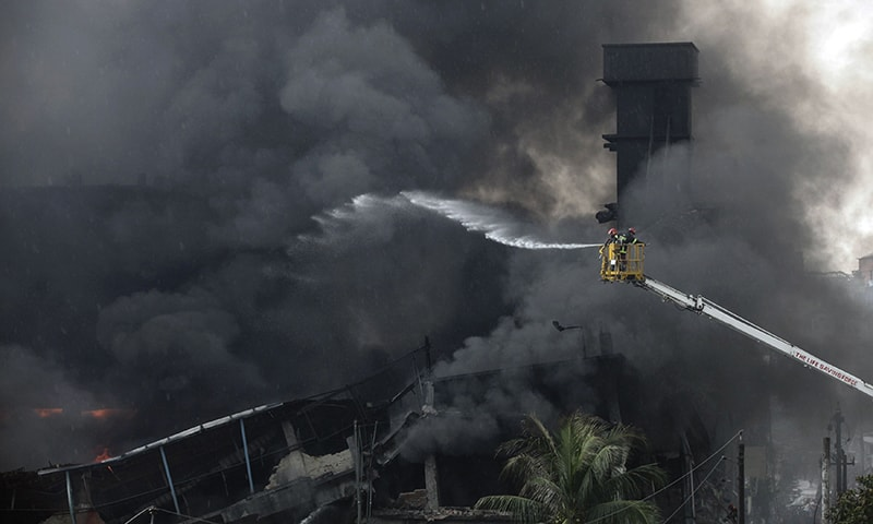Firefighters work to put out a huge fire at the site of an explosion in a factory in the key Bangladeshi garment manufacturing town of Tongi. — AFP