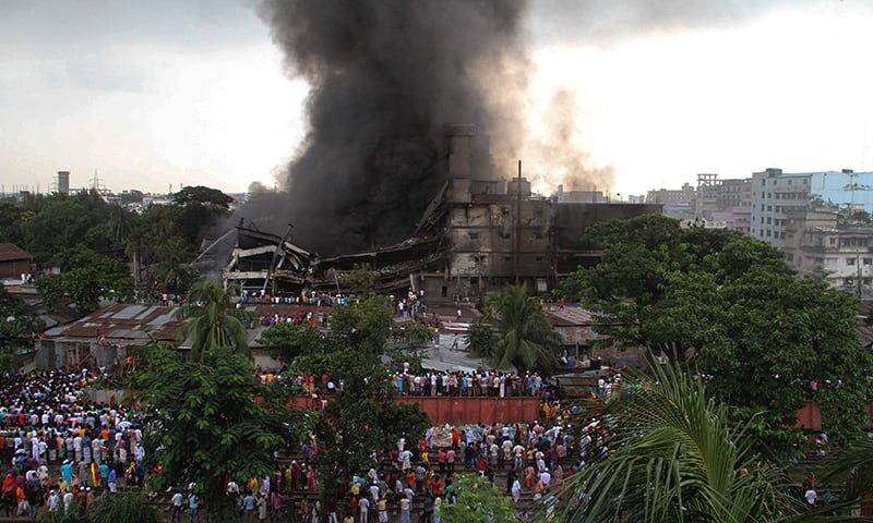 Smoke and flames billow from the burning garment factory. — AFP