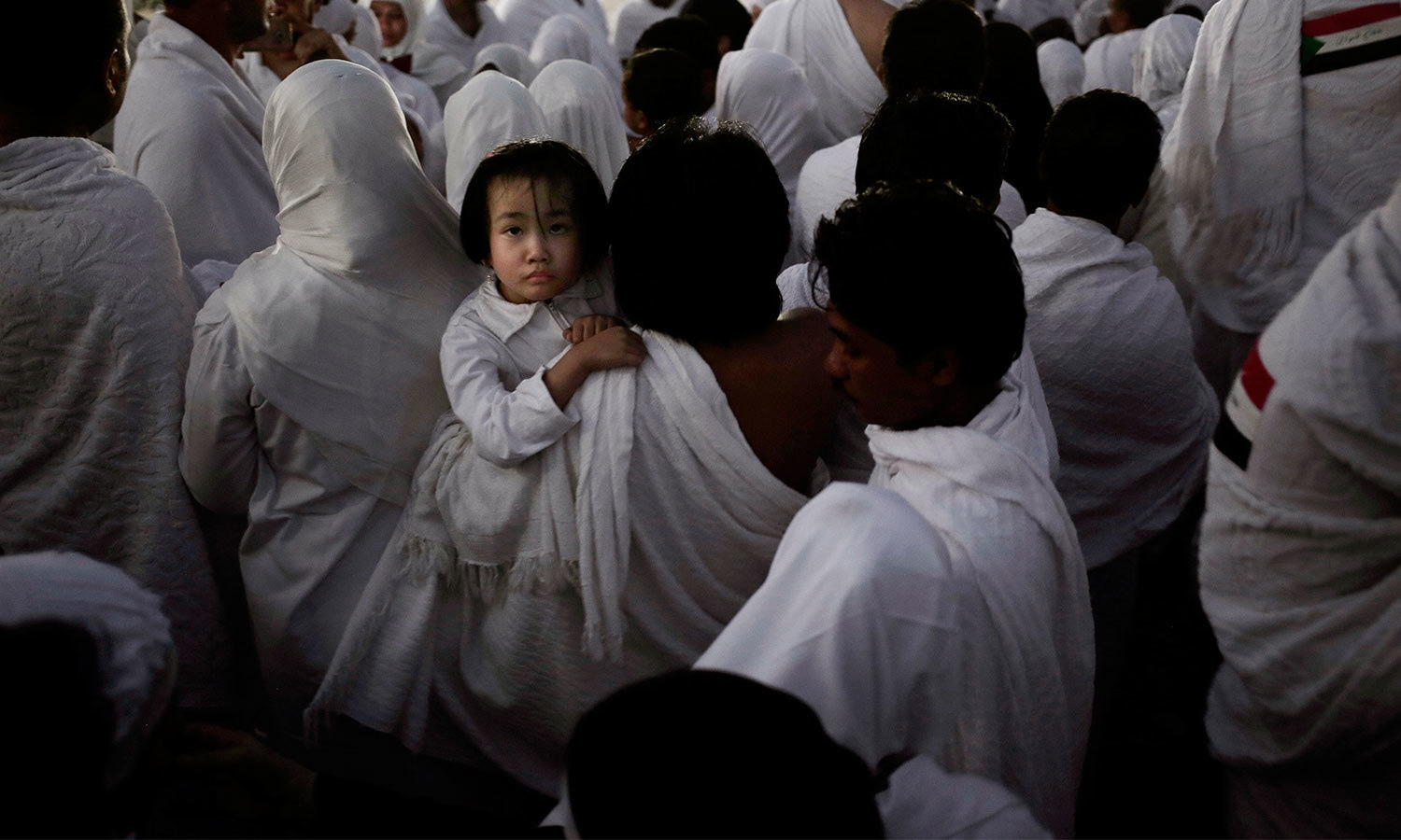 An Indonesian father carries his daughter through the crowd after reaching the top of a rocky hill known as Mountain of Mercy, on the Plain of Arafat. — AP