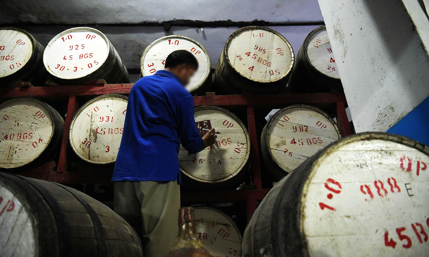 In this photograph taken on June 28, 2016, a worker marks whisky barrels which are stored in the maturation cellar of the Muree Brewery Company in Rawalpindi. ─ AFP