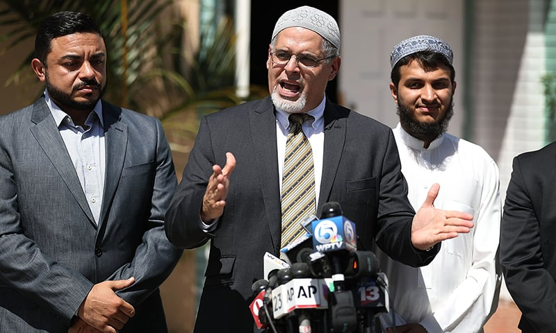 Wilfredo Ruiz, from the Council on American-Islamic Relations, (C) speaks to the media with other officials in front of the Islamic Center of Fort Pierce as law enforcement officials investigate a fire at the centre, which was the mosque attended by the Pulse nightclub gunman, who killed 49 people in Orlando on September 12, 2016 in Fort Pierce, Florida. ─ AFP