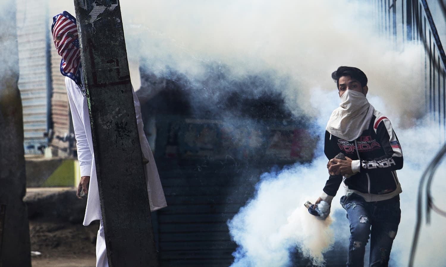 A Kashmiri protester prepares to throw back a tear gas canister at Indian security personnel as another takes cover behind an electric pole during a protest after Eid prayers in Srinagar, India-held Kashmir, Tuesday, Sept. 13, 2016. ─ AP