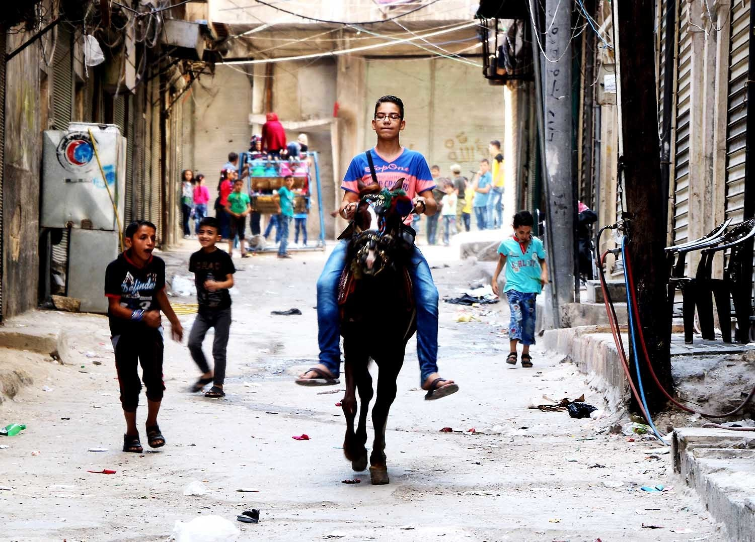 A Syrian boy rides a horse as children play in the street in Aleppo as they celebrate the Eid al-Adha. — AFP