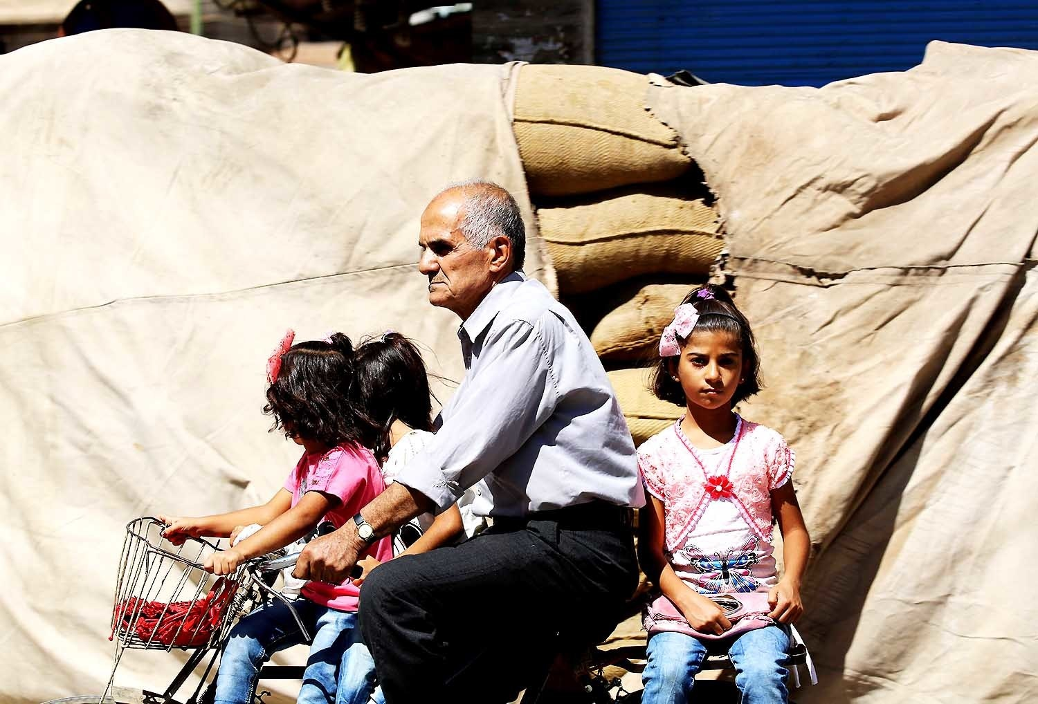 A man carries three girls on a bicycle in Qamishli. — AFP