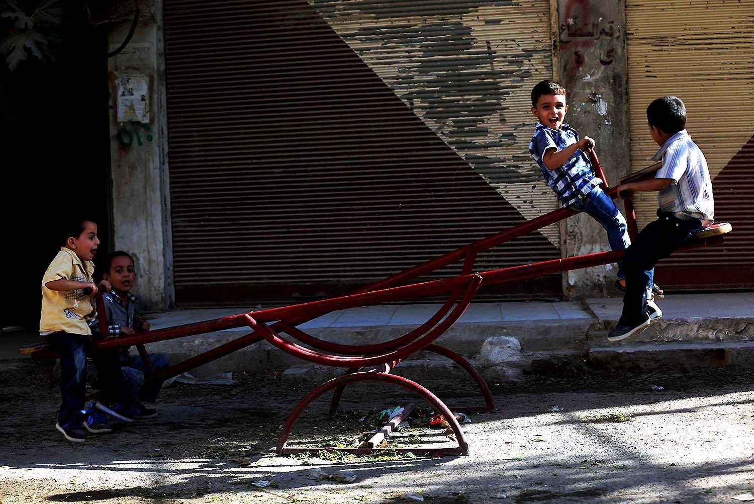 Boys play on a see-saw in Arbin. — AFP