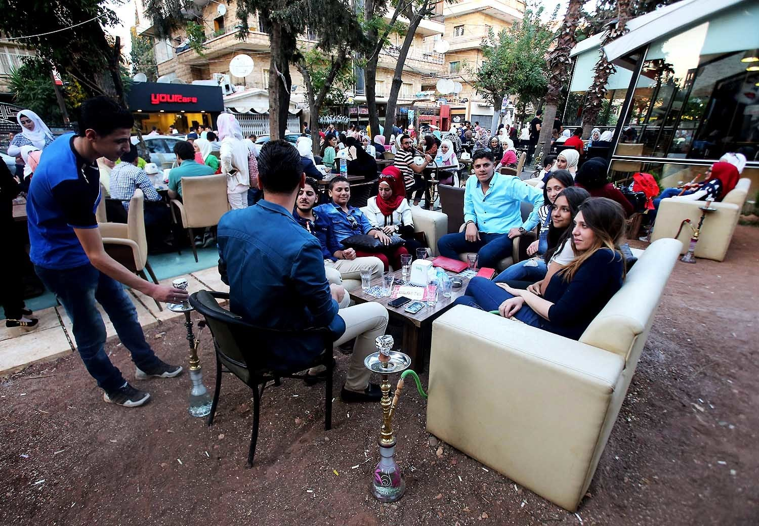 Syrian youths sits at a cafe in the government-held area of Aleppo as they celebrate the Eid al-Adha. — AFP