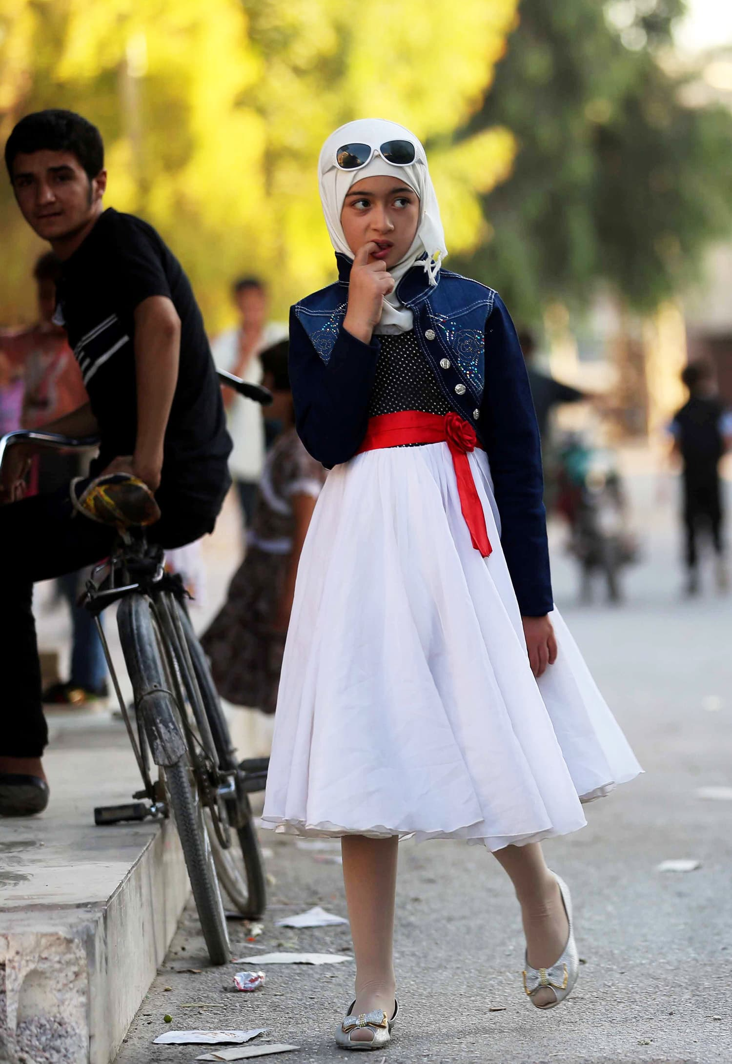 A Syrian girl walks in the street in Arbin.— AFP