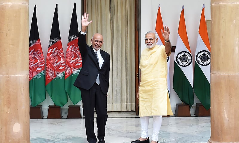 Afghan President, Asharf Ghani and Indian Prime Minister Narendra Modi wave during a photo call prior to a meeting in New Delhi. -AFP