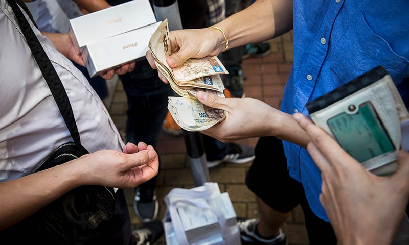 Parallel traders buy and sell the new iPhone 7 during the opening day of sales outside an Apple store in Hong Kong.— AFP