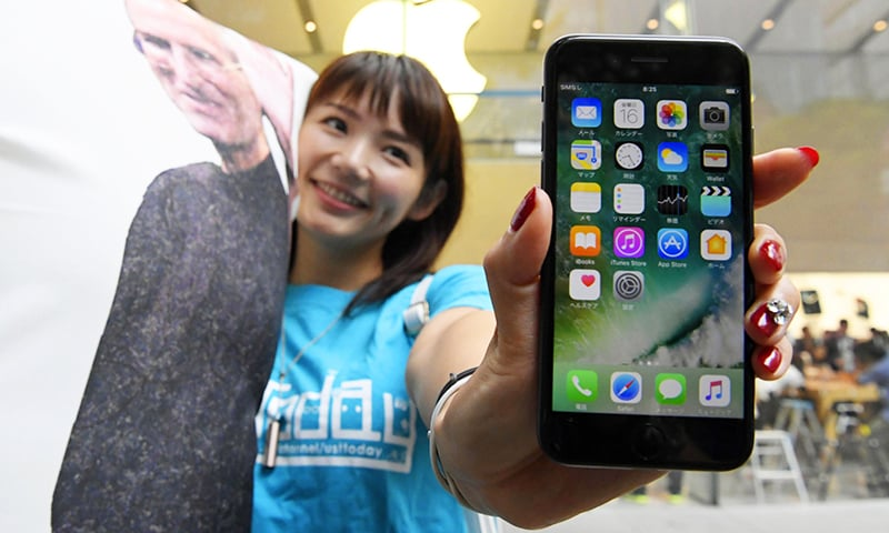 A woman poses with Apple's iPhone 7 after purchase at an Apple store in Tokyo.— AP