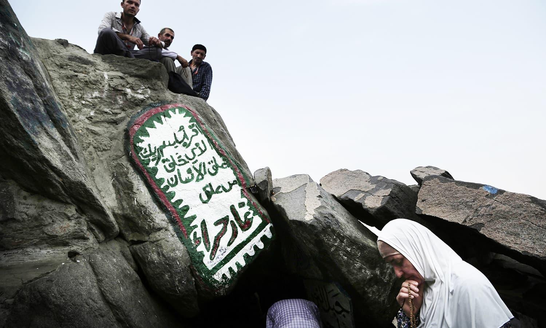 A Turkish Muslim woman prays outside Hira cave, on the outskirts of Makkah, Saudi Arabia. — AP