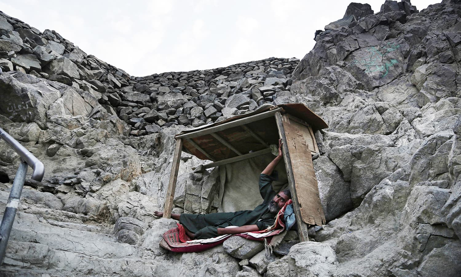 A Pakistani beggar who sleeps on Noor Mountain poses for a portrait.— AP