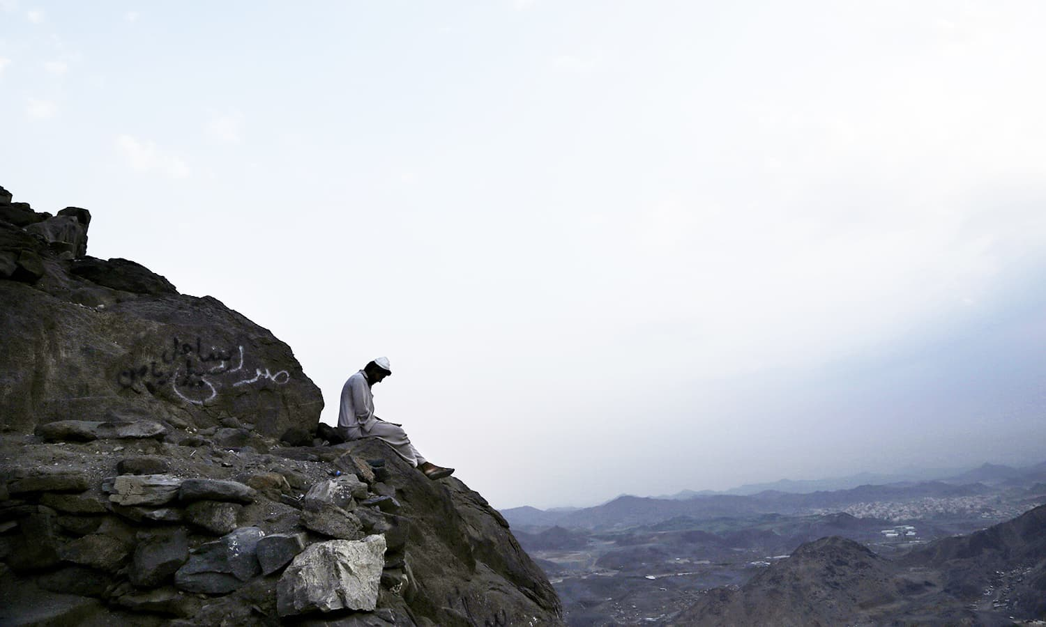 A Pakistani man living near Hira cave reads before sunrise on Noor Mountain.— AP