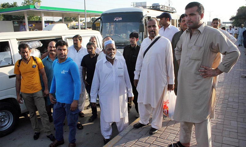 RAWALPINDI: Pakistani workers, who were stranded in Saudi Arabia after losing their jobs, stand outside the airport after their return from Dammam on Friday.—Online