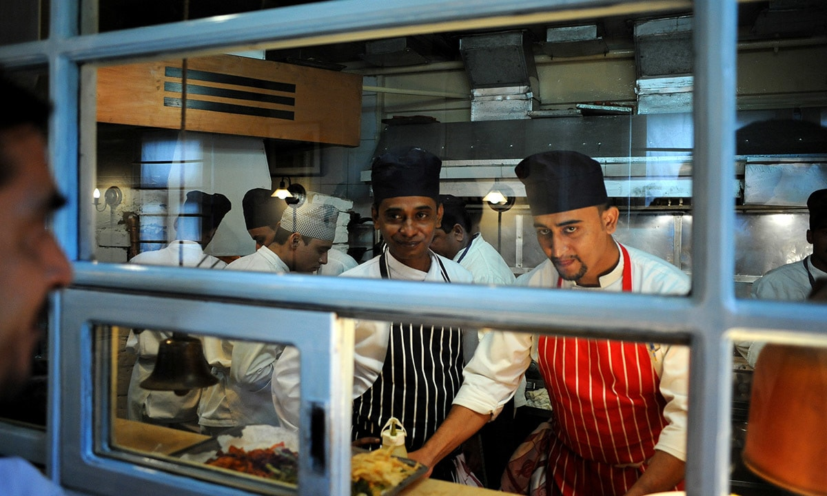 Okra's head chef Mukesh Devtani (left)  looks out from the open kitchen