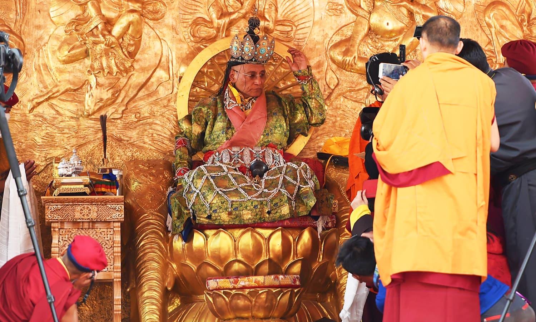 The head of the Drukpa Lineage, Gyalwang Drupa, wearing sacred six-bone ornaments, gestures to media. — AFP