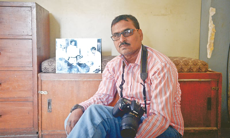 LENSMAN Muhammad Azeem is seen with the photograph of fatally wounded Mir Murtaza Bhutto that he had taken on Sept 20, 1996 after a 'police encounter' in Clifton.—Fahim Siddiqi / White Star