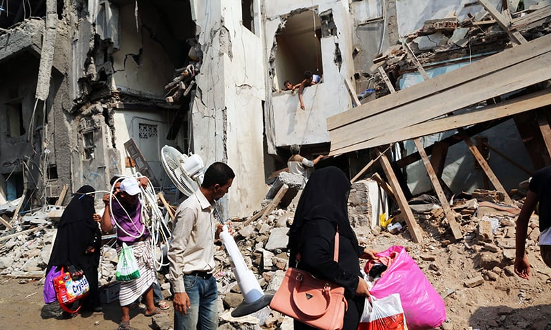 Yemenis carry belongings they recovered from the rubble of buildings destroyed during Saudi-led air strikes. -AFP