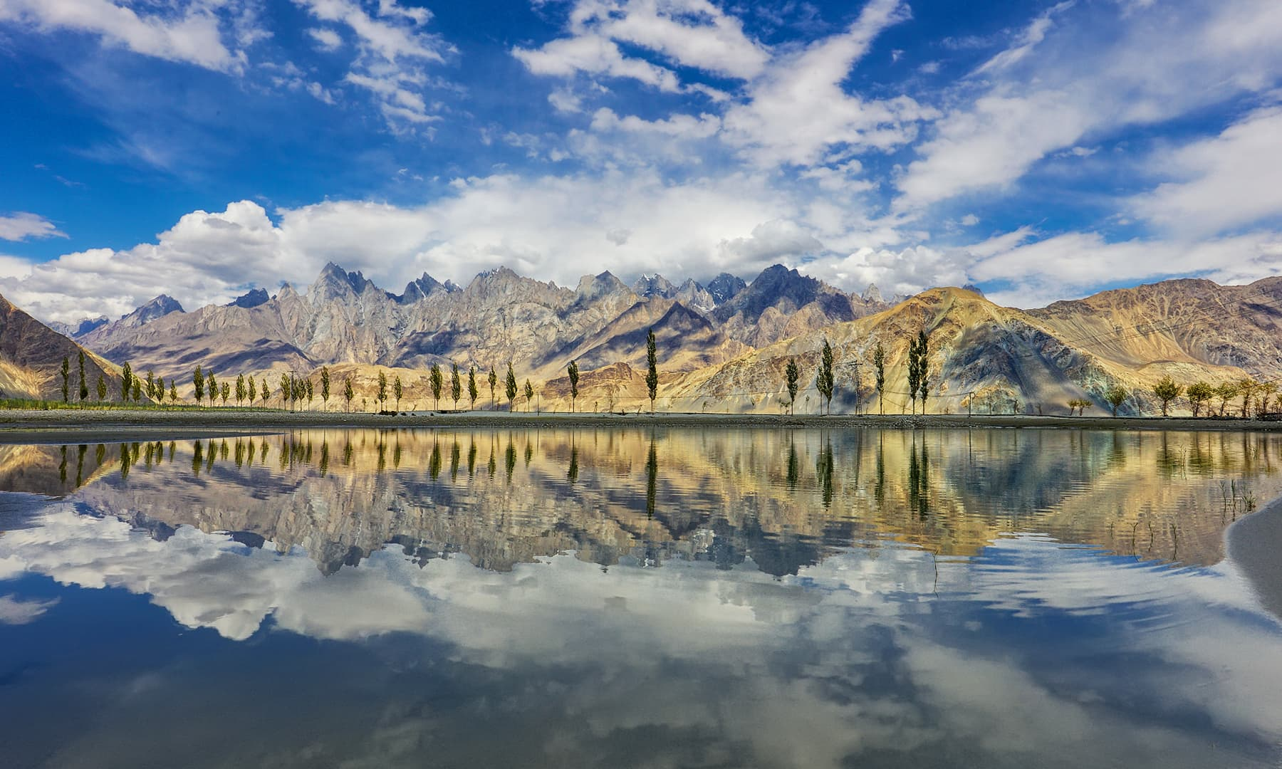 The snow-capped mountains in Skardu are a stunning backdrop to the lake.