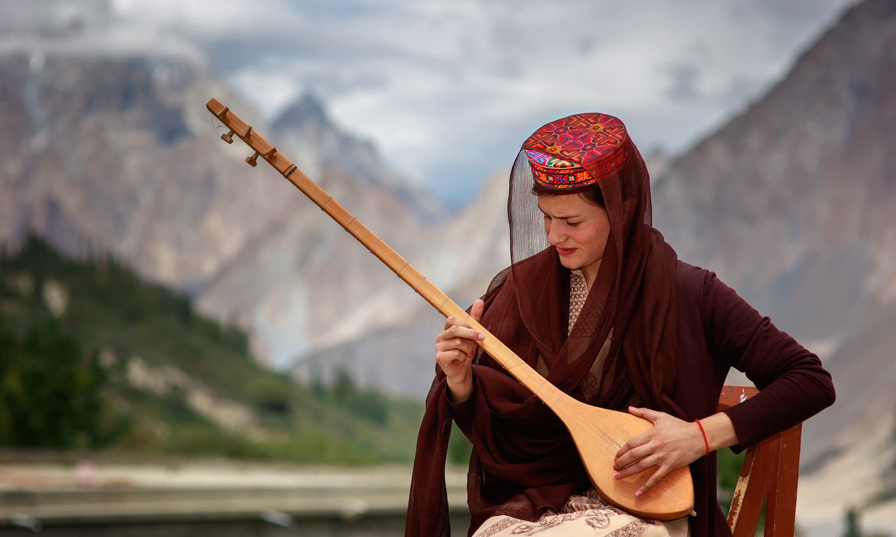 A girl practices a traditional musical instrument outdoors.