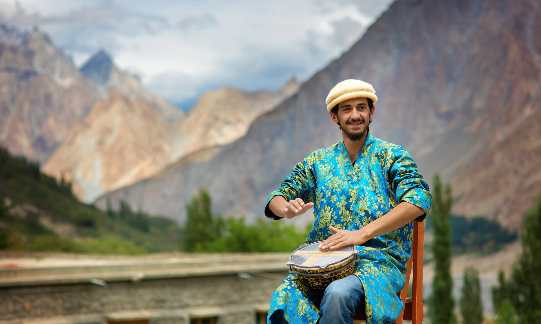 A student happily plays the drums.