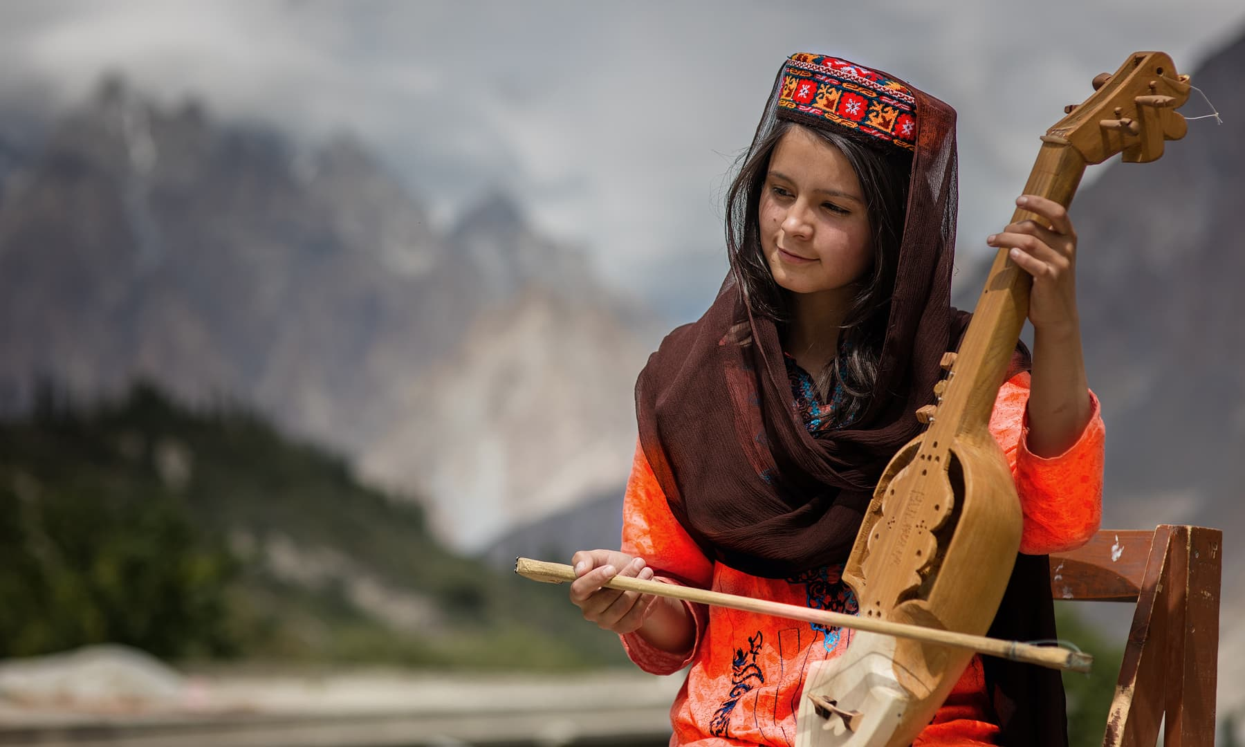 A young girl plays the rabab.