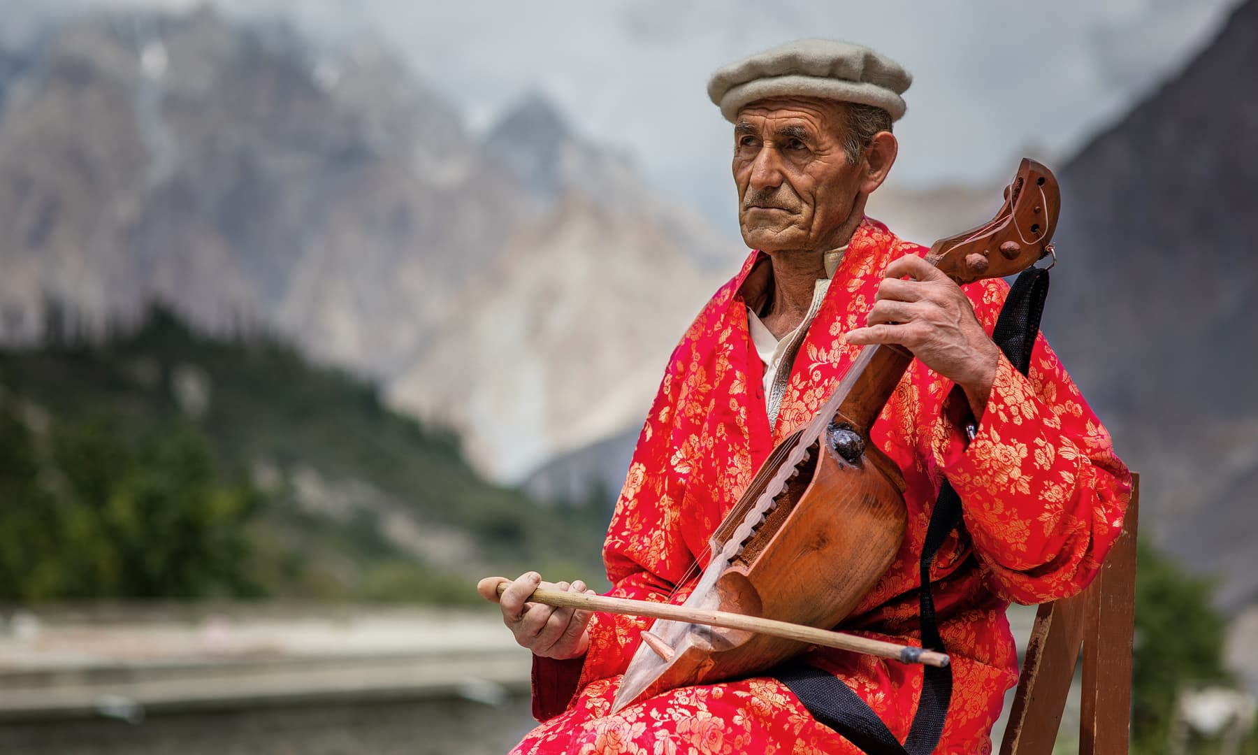 A man plays the rabab with full concentration.