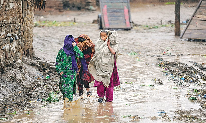 A displaced girl carries her brother during rainfall on the outskirts of Islamabad.—White Star