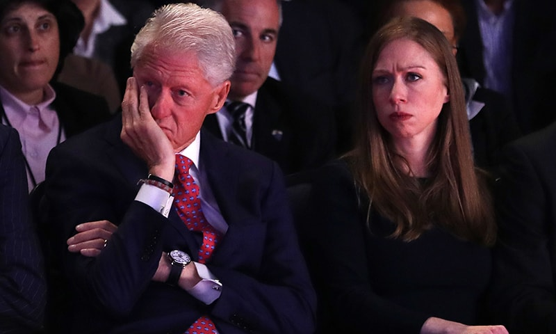 Husband and former US President Bill Clinton and daughter, Chelsea Clinton listen as Democratic presidential nominee Hillary Clinton speaks during the Presidential Debate .— AFP