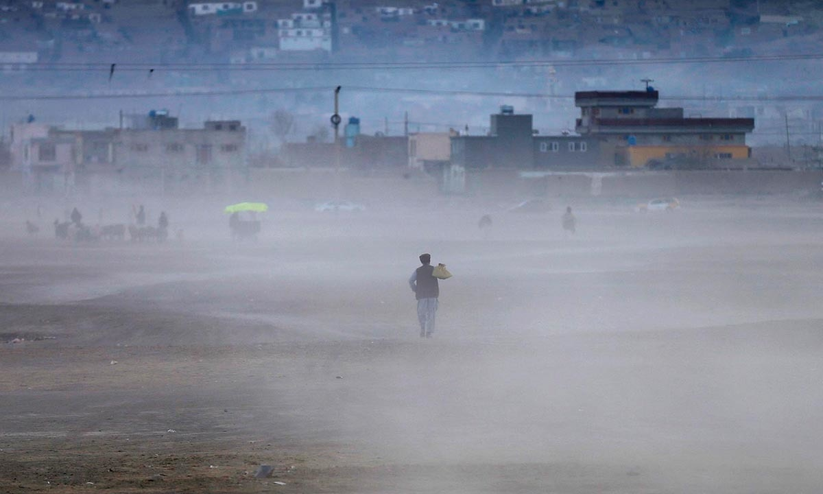 An Afghan man walking through a dust cloud as the sun sets in Kabul | Mohammad Ismail, Reuters