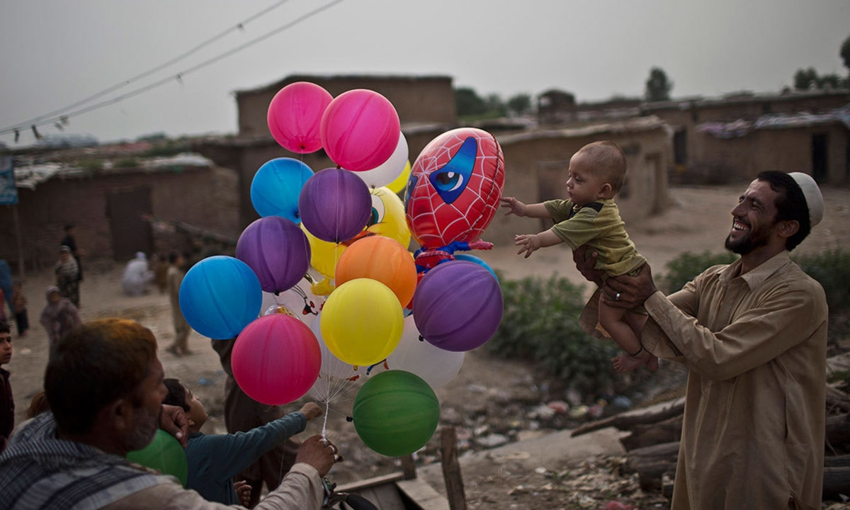 A man displaced by the military operation in the tribal areas plays with his child, on the outskirts of Islamabad | AP