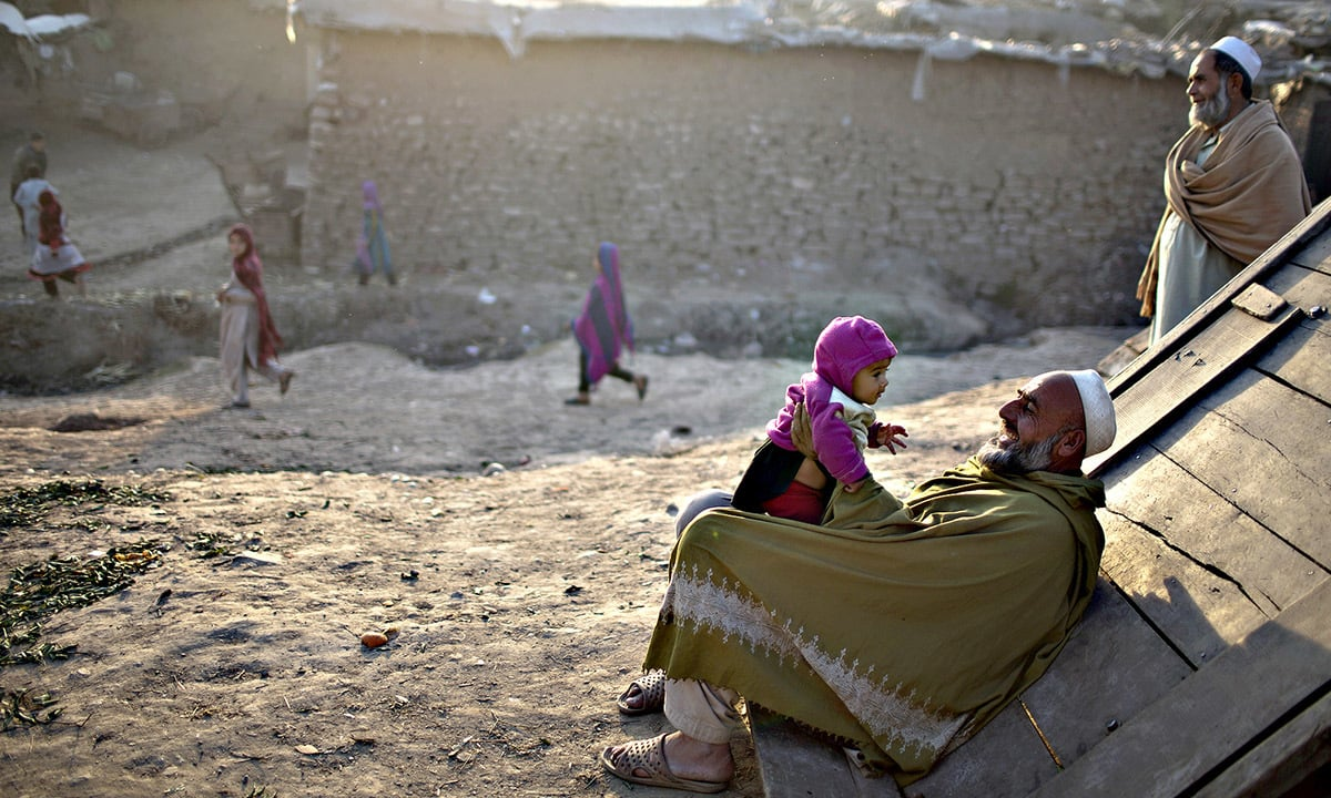 An Afghan refugee plays with his son on the roadside on the outskirts of Islamabad | Muhammed Muheisen, AP