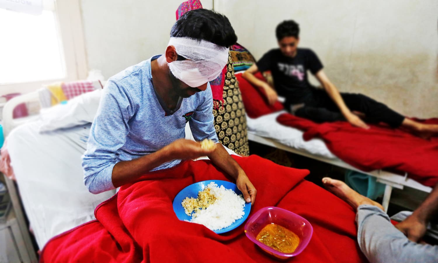 A man who was injured in clashes between Indian police and protesters eats his food inside a hospital ward in Srinagar, Sept 21, 2016. ─ Reuters