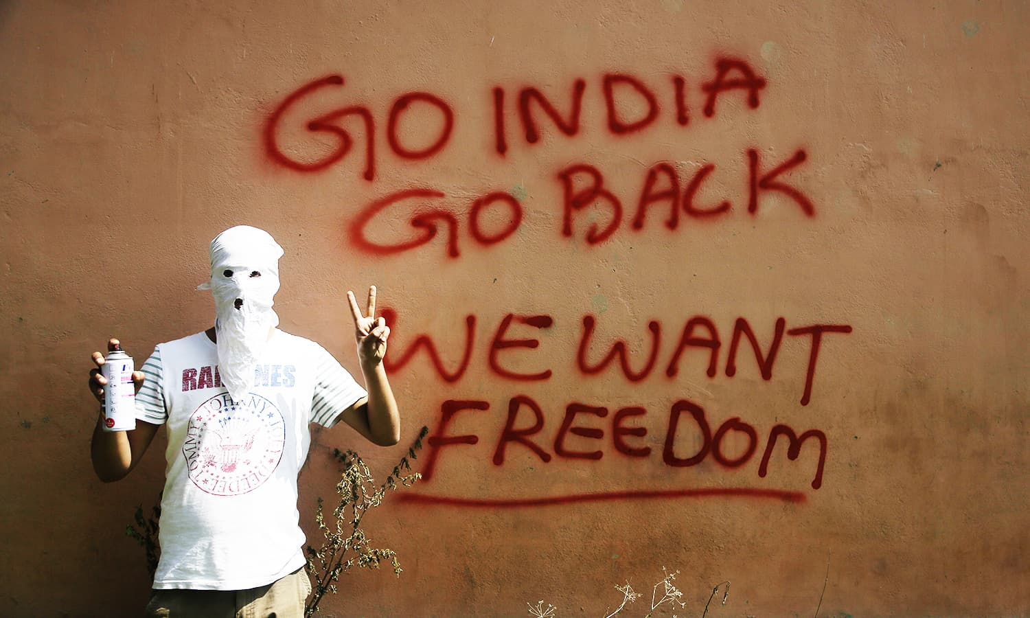 A masked Kashmiri protester shows the victory sign after drawing graffiti on the wall of a building in Srinagar. ─ AP