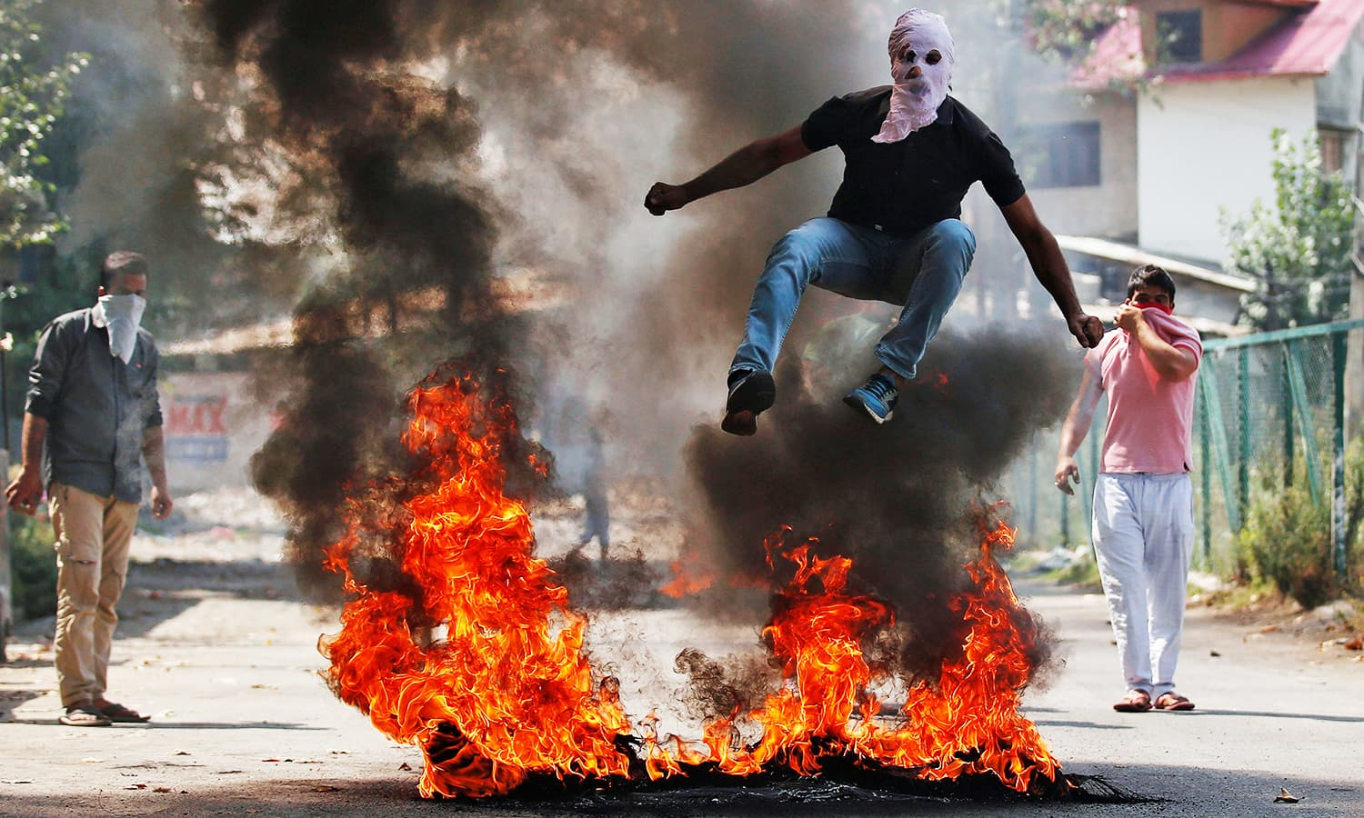 A man in a balaclava jumps over burning debris during a protest against the recent killings in IHK, in Srinagar, Sept 12, 2016. ─ Reuters