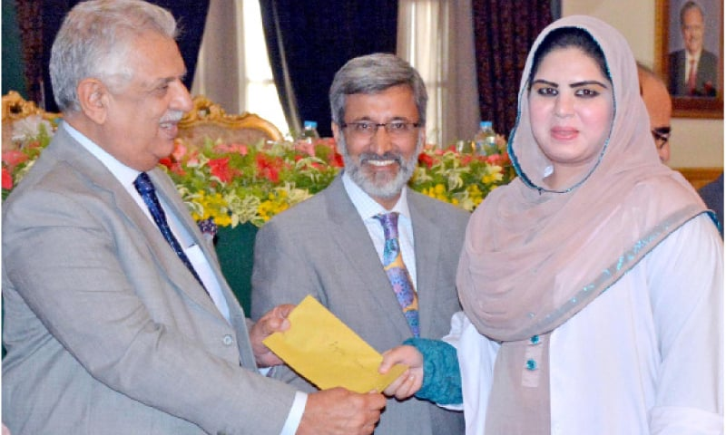 KP Governor Iqbal Zafar Jhagra gives away cash prize to a student at a ceremony at Governor House, Peshawar, on Wednesday. — INP