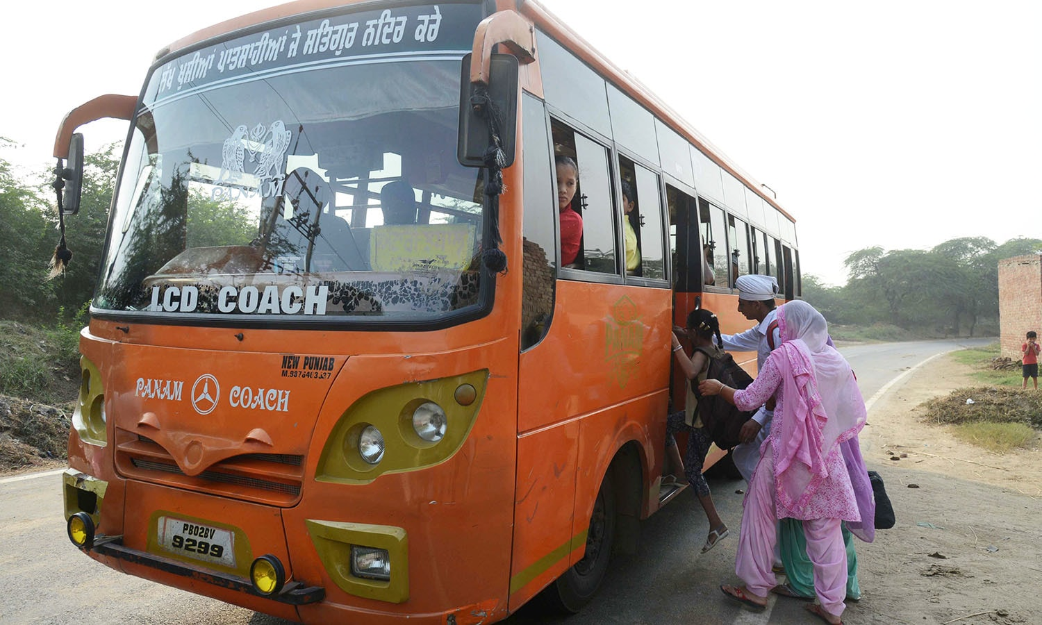 Indian villagers from the India-Pakistan border area board the bus as they evacuate from the border village of Neshta. — AFP