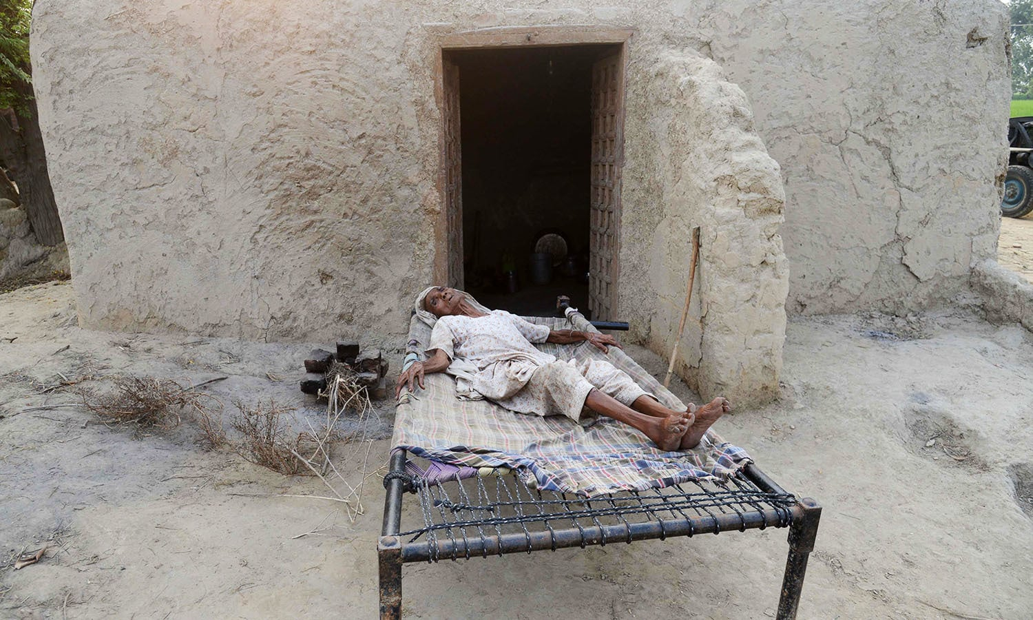Elderly Indian villager, Teeja Kaur takes a rest on a bed at the border village Dauke. — AFP