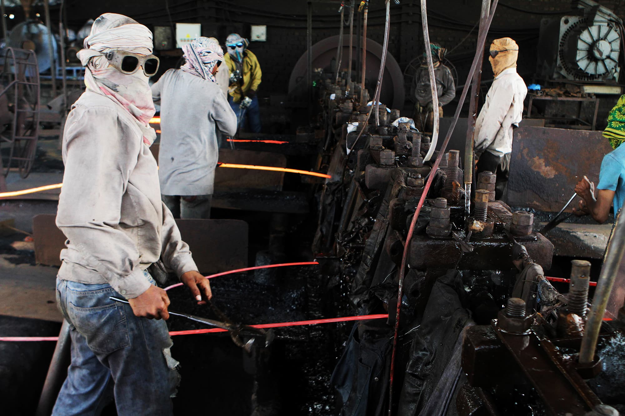 Colleagues of Mubeen Rajhu work at a steel mill in Lahore. — AP
