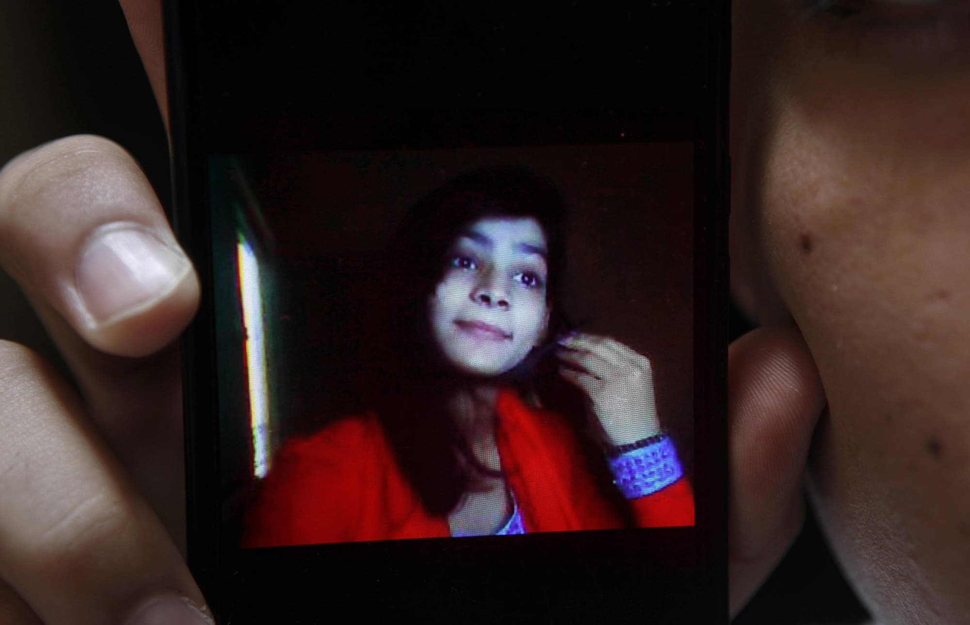 Hassan Khan shows a picture of his wife Zeenat Rafiq, who was burned alive, allegedly by her mother, on a mobile phone at his home in Lahore. — AP