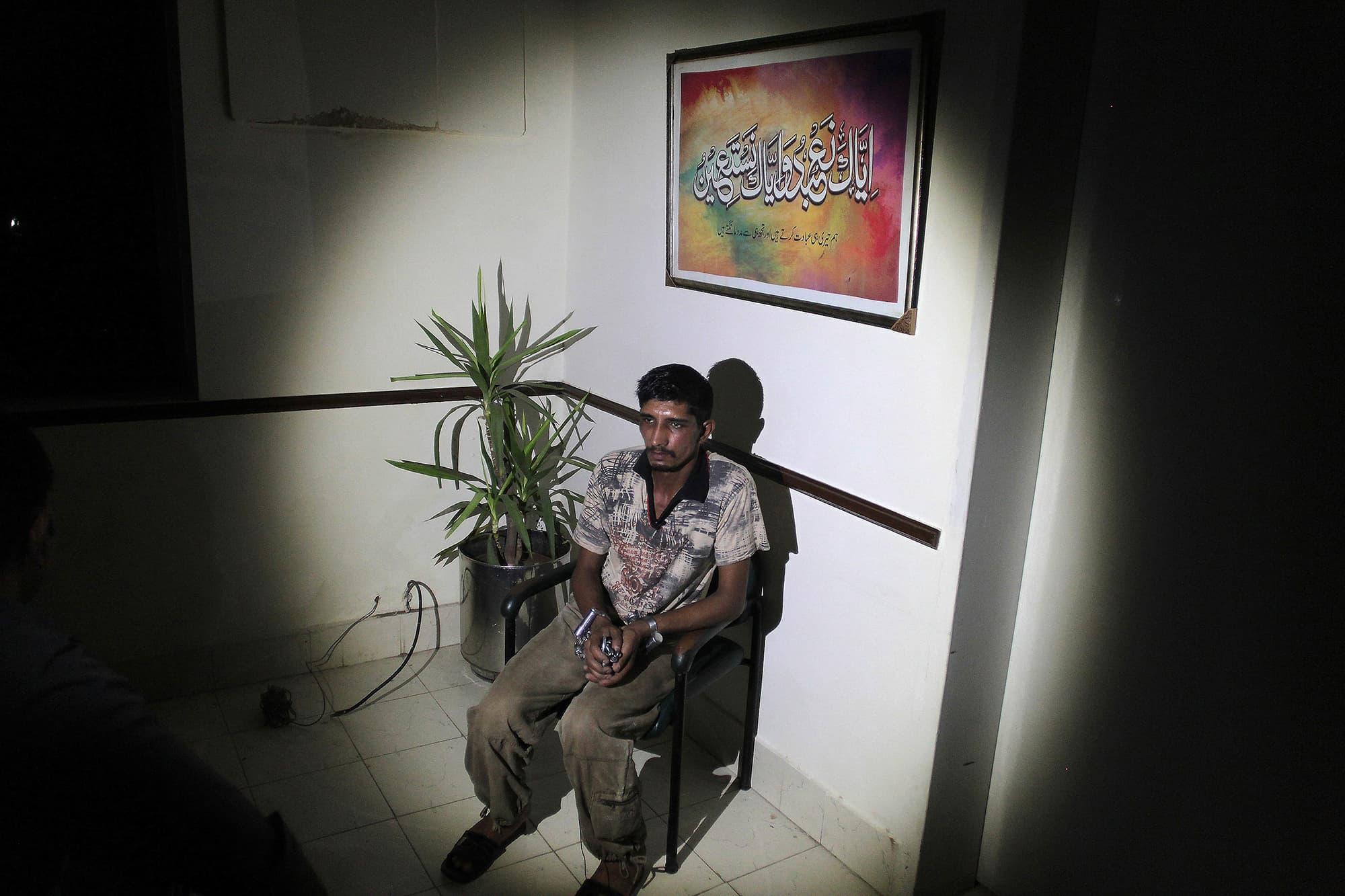 Mubeen Rajhu talks at police headquarters in Lahore. — AP