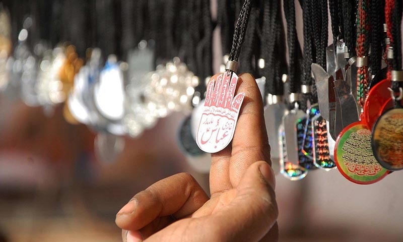 Man checking religious items displayed on a stall in Islamabad —Online