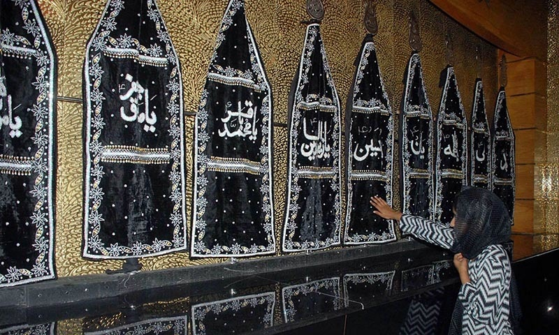 A mourner showing her respect as she touches the Alam of Imam Hussain (RA) in Islamabad. —Online