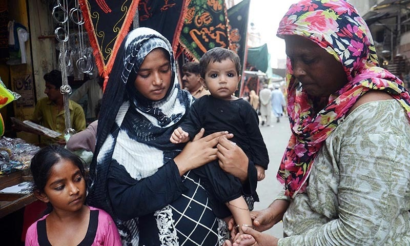 Woman seen securing a ring on a leg of an infant as a religious ritual in Lahore. -Online