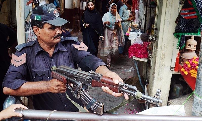 Policeman standing alert to avert any untoward incident at Bibi Pak Daman Bazaar in Islamabad. —Online