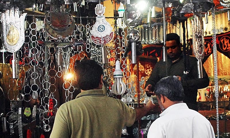 Customers buying religious items from a shop in the area of Shah Chan Charagh in Rawalpindi. —Online